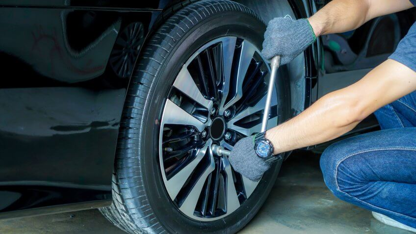 Car mechanic using tools to remove the wheel nuts to check and repair in the car repair center.