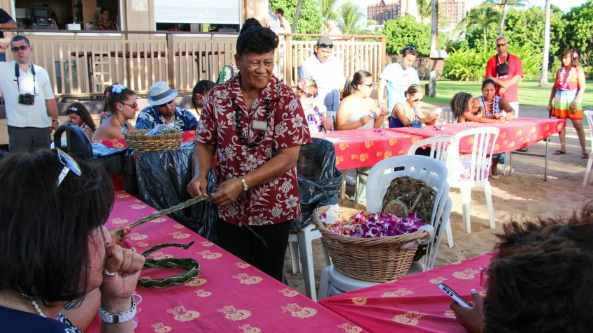 A demonstration of the art of making Hawaiian Lei from ti leaves and orchid flowers, Oahu, Hawaii.