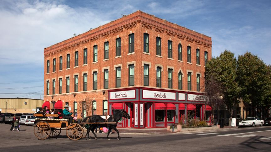 Pueblo, Colorado, USA - October 29, 2011: An old fashioned horse drawn carriage filled with kids and driven by a cowboy rolls onto North Union Ave.