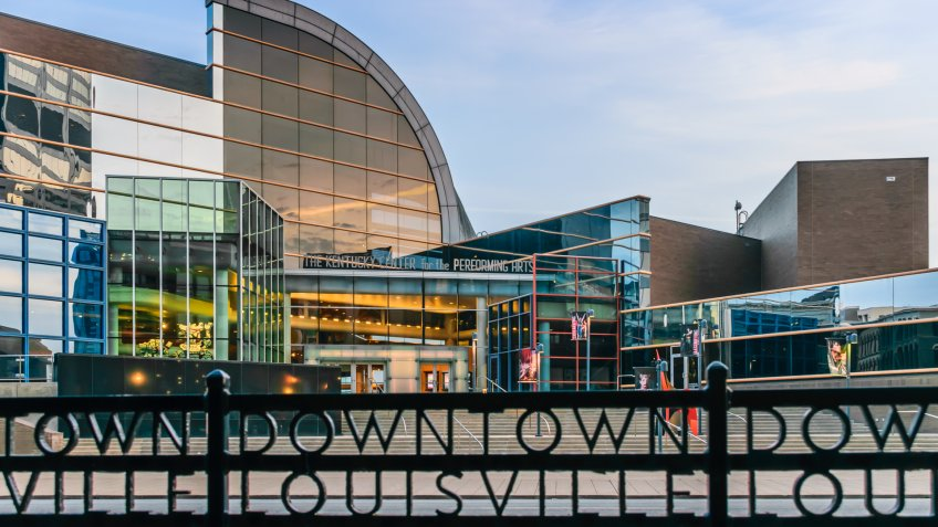 "Louisville, Kentucky, USA - March 27th 2016: Kentucky Center for the Performing Arts building in Louisville Kentucky with rod iron fence which states ""Downtown Louisville"" in foreground."