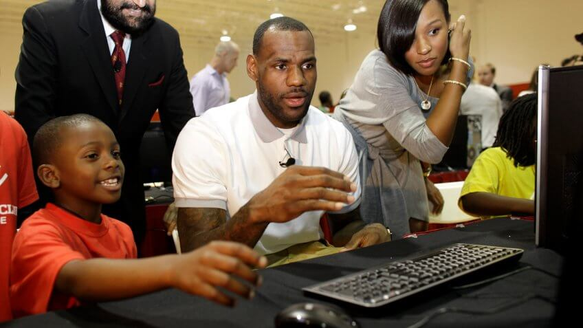 LeBron James, Savannah Brinson, Cam'ron Lightbourne Miami Heat basketball player LeBron James, center, sits with Cam'ron Lightbourne, 8, left, and his girlfriend Savannah Brinnson, right, at a new computer during a charity event at the Northwest Boys & Girls Club in Miami, .