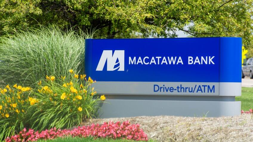"""""""Holland, Michigan/United States of America - 07/17/2019: Blue Macatawa Bank Sign with drive thru, atm and flowers on green grass and blue sky."""