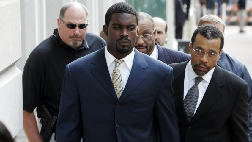 Atlanta Falcons football player Michael Vick arrives with his attorney Billy Martin, right, at federal court.