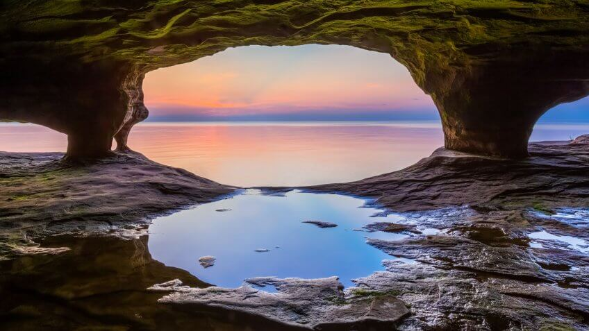 A colorful sunset sky over Lake Superior is photographed from within a sea cave on Michigan's northern coast near Pictured Rocks National Lakeshore.