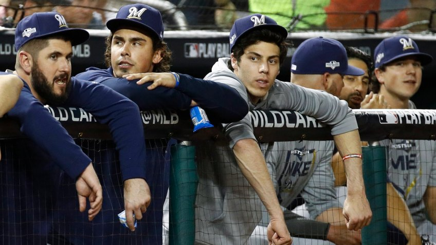 Milwaukee Brewers' Christian Yelich, third from left, sits in the dugout in the fifth inning of a National League wild card baseball game against the Washington Nationals, in WashingtonBrewers Nationals Baseball, Washington, USA - 01 Oct 2019.
