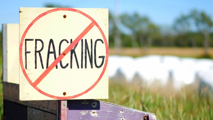 Hand-painted No Fracking Sign in Rural Setting, farmland and hay bales in background.