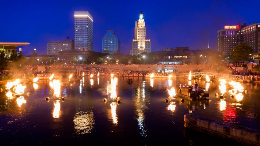 """Providence, Rhode Island, USA - June 30, 2011: A boat of volunteers, clad all in black, kick off the last Waterfire of July 2011 by lighting the first brazier."