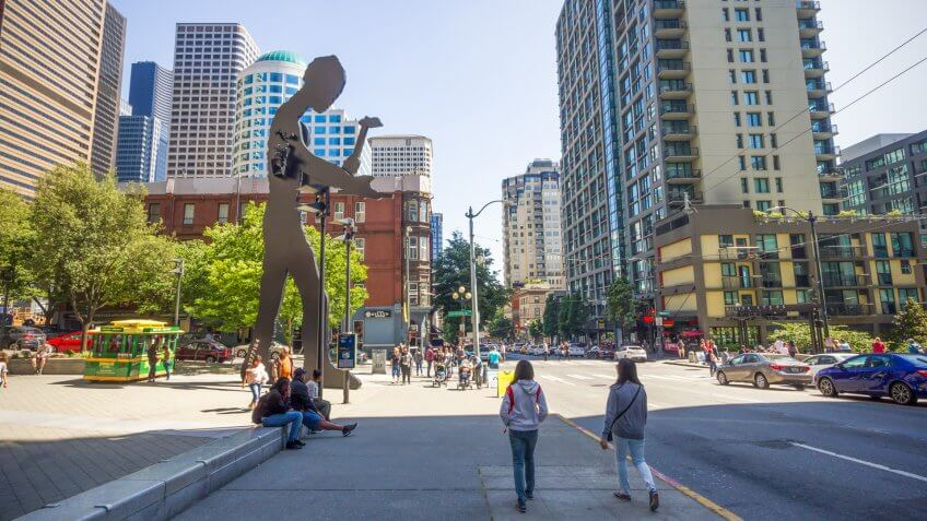 Seattle, Washington, USA - July 2,2017 : People walking on a sidewalk in front of the Seattle Art Museum, which have the hammering man and a skyscraper in the background, Washington, USA.