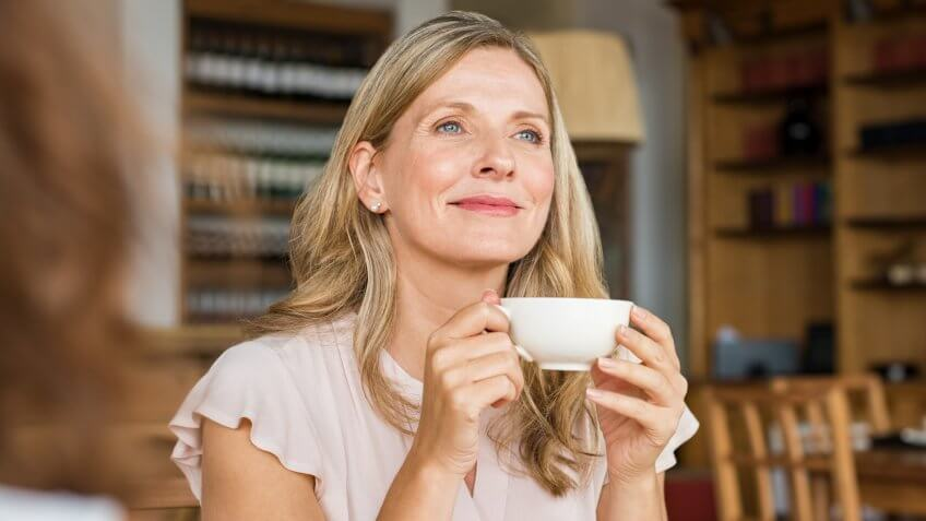 Mature woman holding coffee cup and looking away at cafeteria.