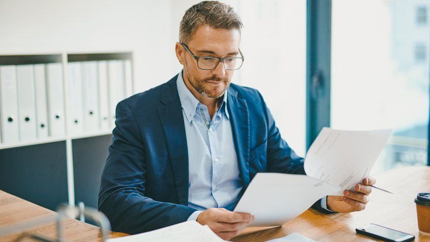 Shot of a mature businessman reading a document at his desk in an office.