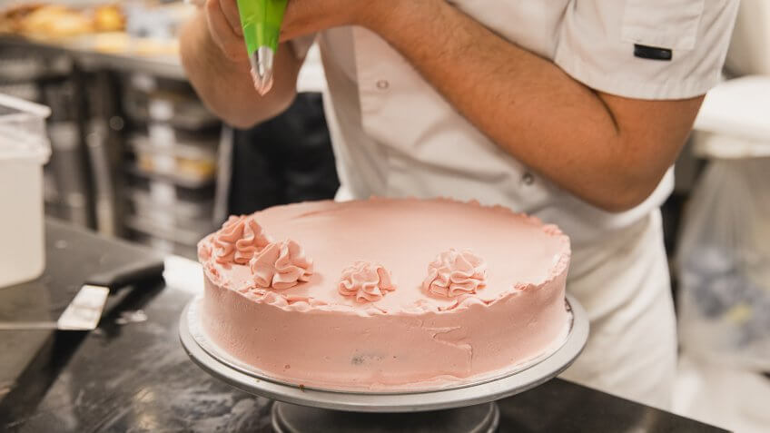 Cropped image of pastry chef in whites icing cake, concentration, skill, care, homemade.
