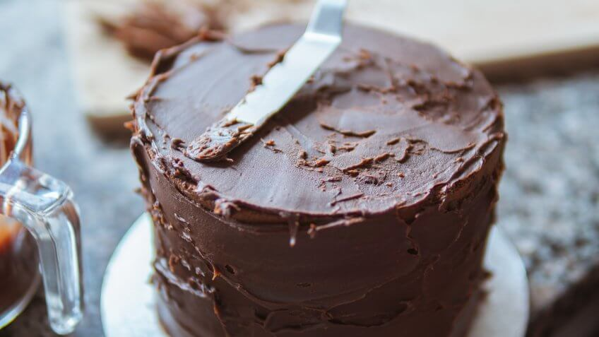 A close-up photograph of a girl decorating a cake with chocolate ganache in a domestic kitchen.