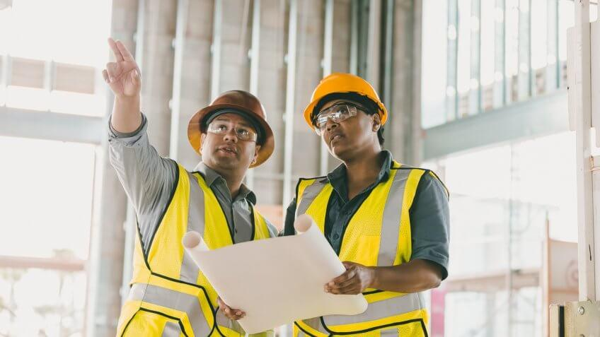 Two multi-ethnic construction workers discussing floor plans.