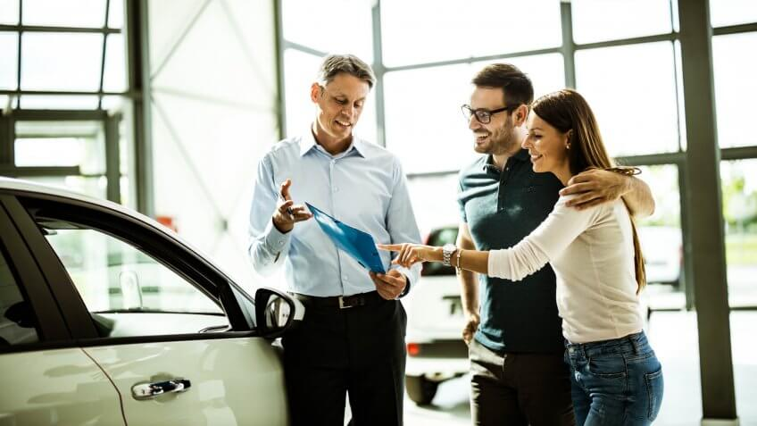 Happy embraced couple and car salesperson going through paperwork while buying a car in a showroom.