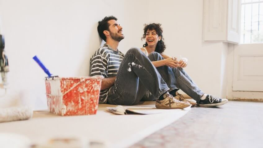 Couple is resting and having fun after hard work painting their apartment.