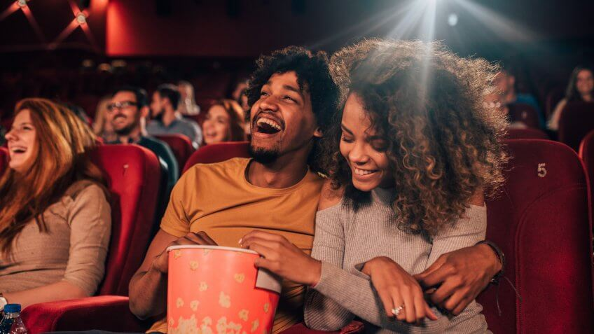 Joyful young people hugging and eating popcorn art the cinema.