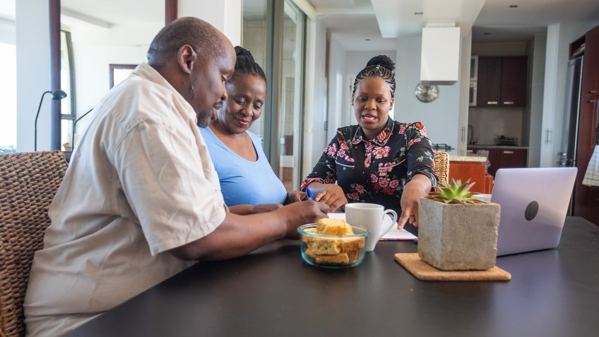 Senior African Couple Getting Retirement Financial Advice at the Dining Room Table.