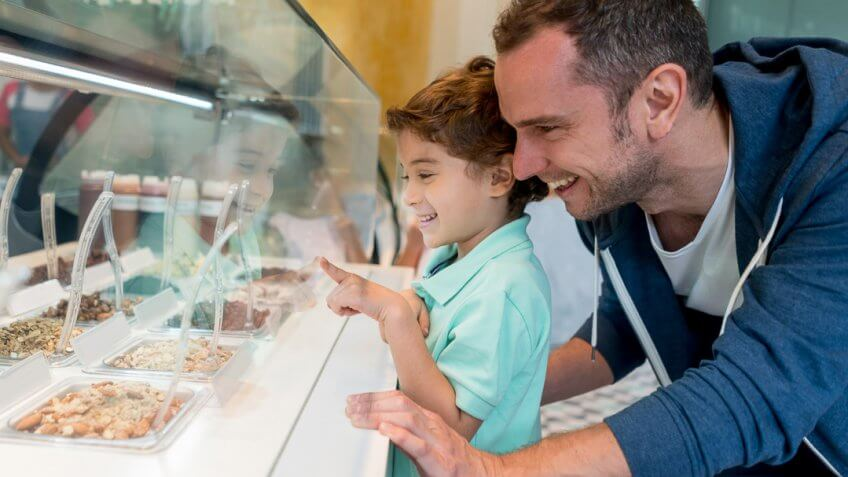 Happy father and son at the ice cream shop choosing the toppings for their sundae - lifestyle concepts.