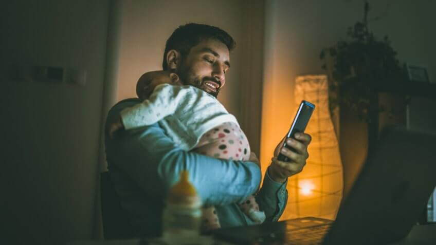 Young father working at home with his baby  girl.