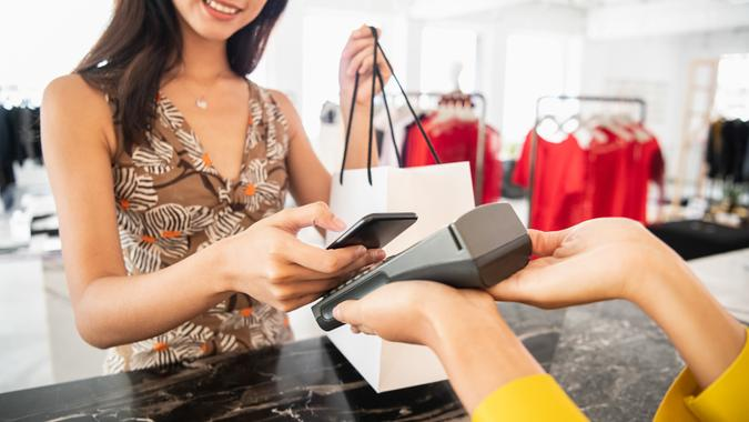 Cropped image of female in her 20s using smart phone to pay for clothes in modern boutique, shop worker holding electronic reading device, technology, convenience, shopping, retail.