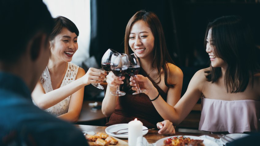 Group of joyful young Asian woman having fun and toasting with red wine during party.