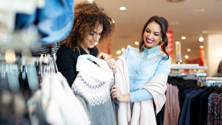 Two cheerful girls shopping for clothes.