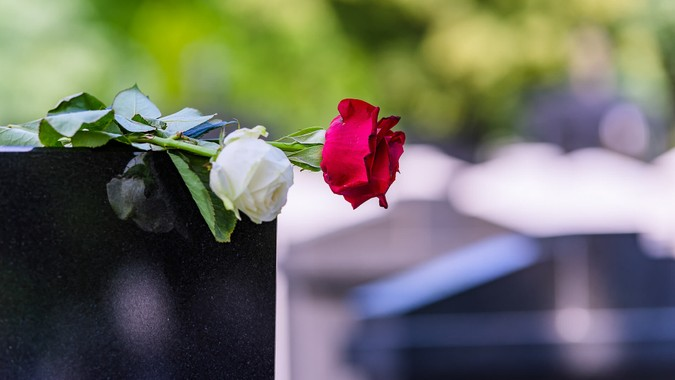 Close View of Headstone In Cemetery With Red Rose Flower.