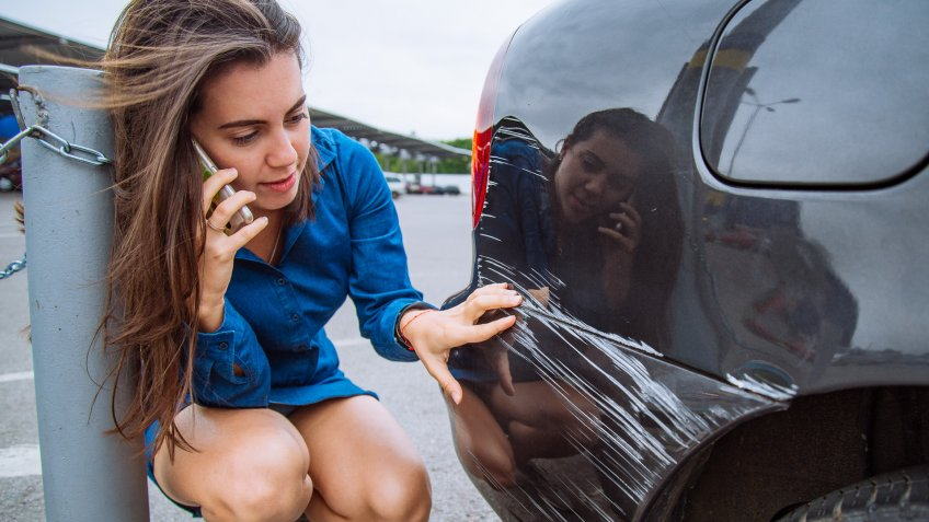 woman stand near scratched auto.