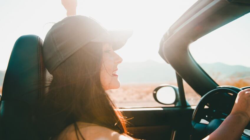 Young beautiful woman driving a convertible car in the desert of Death Valley, California.