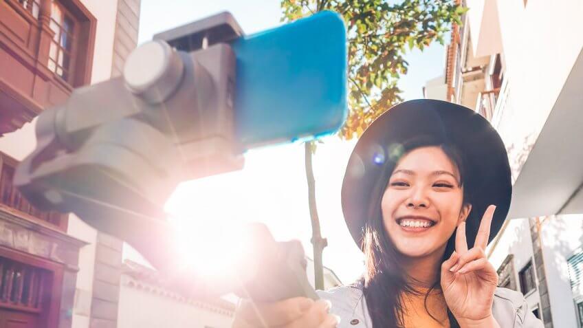 girl using selfie stick recording a video