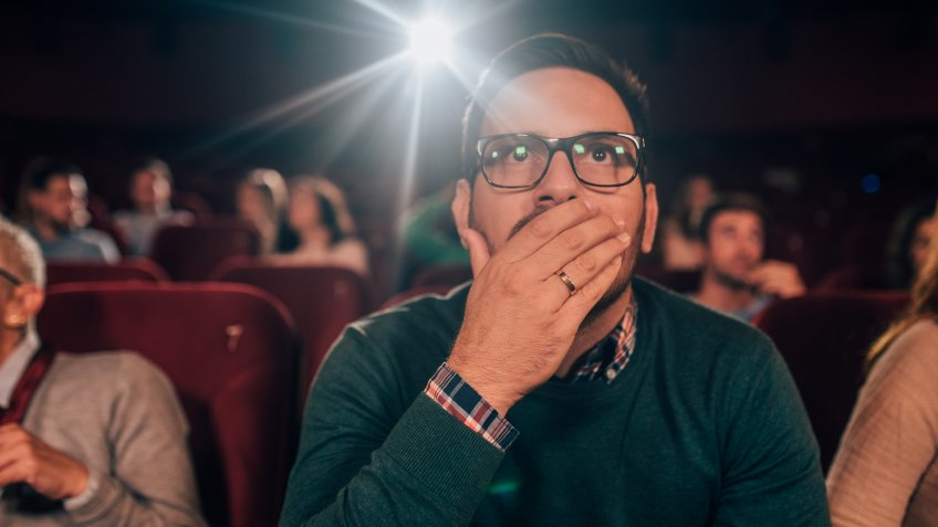 Young man watching a horror movie at the cinema.