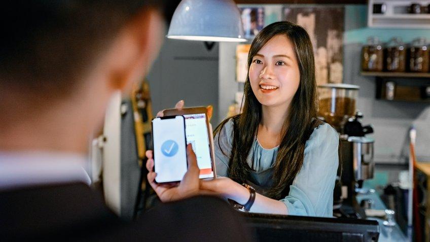 Smiling female cashier holding digital tablet at checkout.