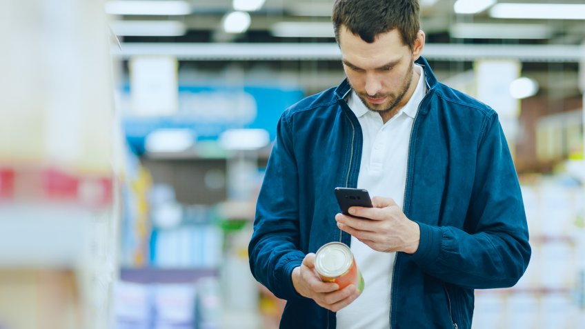 At the Supermarket: Handsome Man Uses Smartphone to Check Nutritional Value of the Canned Goods and Buy it.