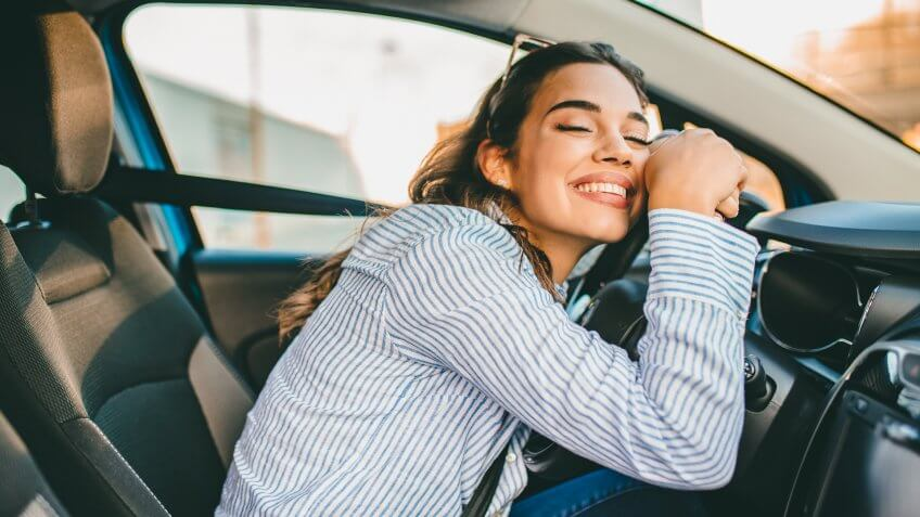 Young Woman Embracing Her New Car.