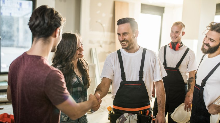 Happy manual worker welcoming young couple to their renovated apartment.