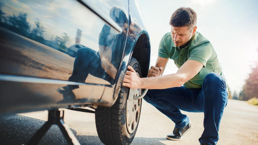 Man changing wheel after a car breakdown.