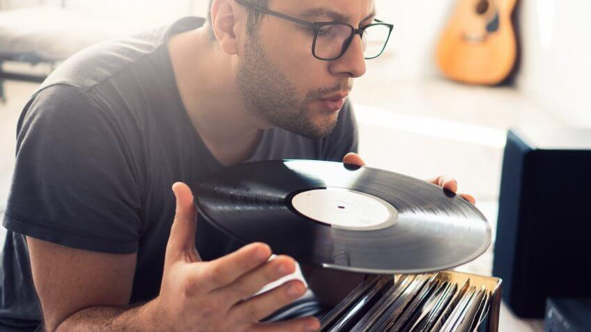 Young guy is cleaning dust from his vinyl records.