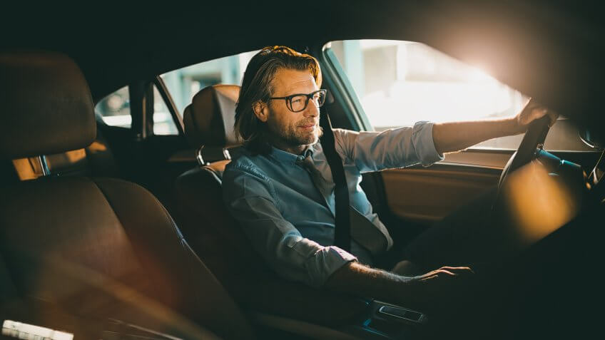 Close up photo of a businessman driving a car.