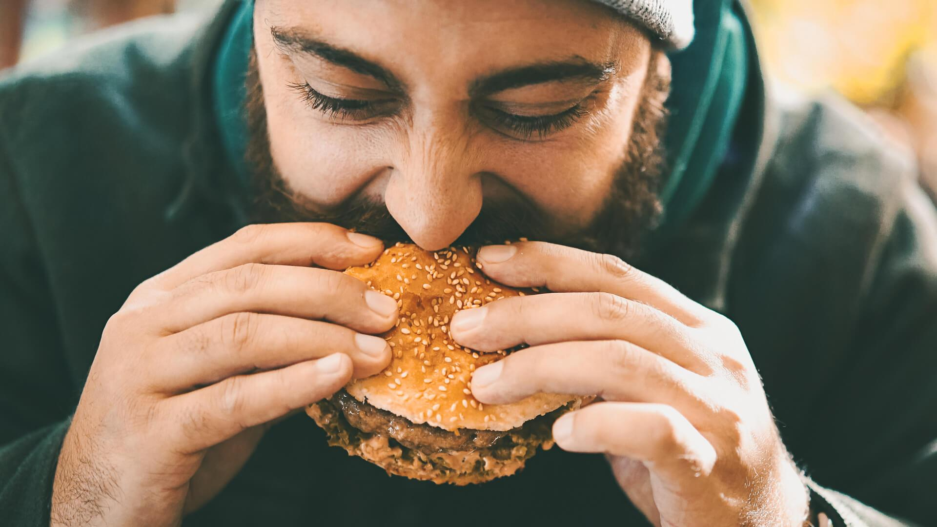 Closeup front view of a mid 20's man biting on a juicy burger outdoors.