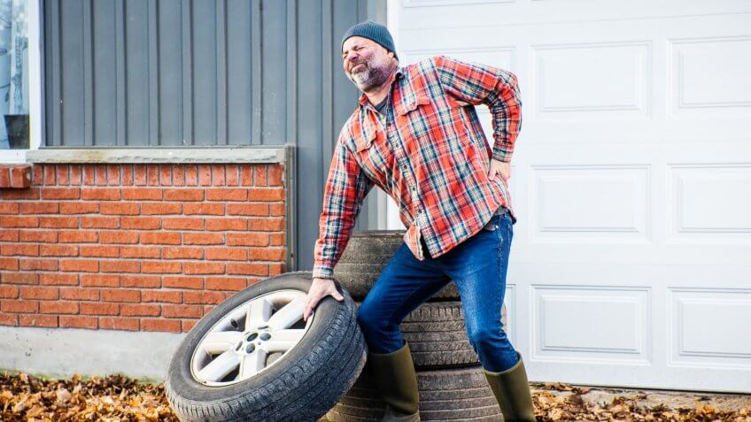 A man straining and injuring his back lifting a large truck tire improperly.