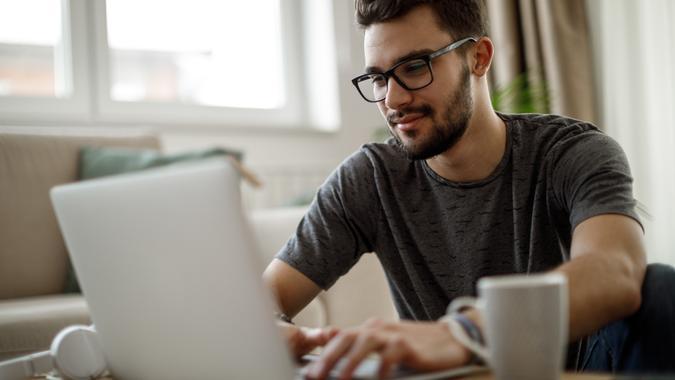 Teenage boy using laptop at home.
