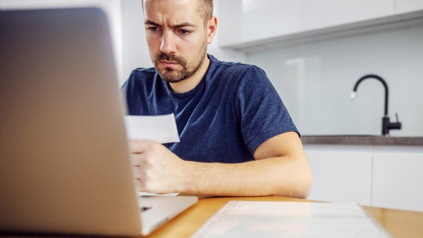 Young frowning bearded serious man sitting at dining table, holding bill and using laptop for paying it.
