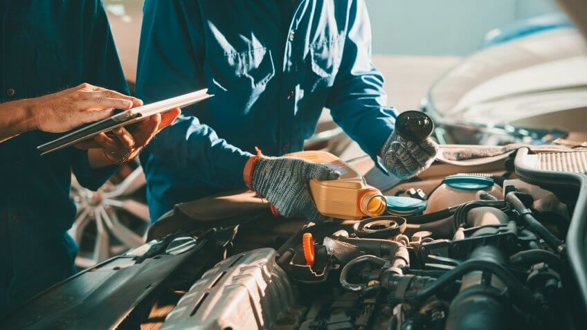 Mechanic pouring oil in car engine when his colleague using tablet computer.