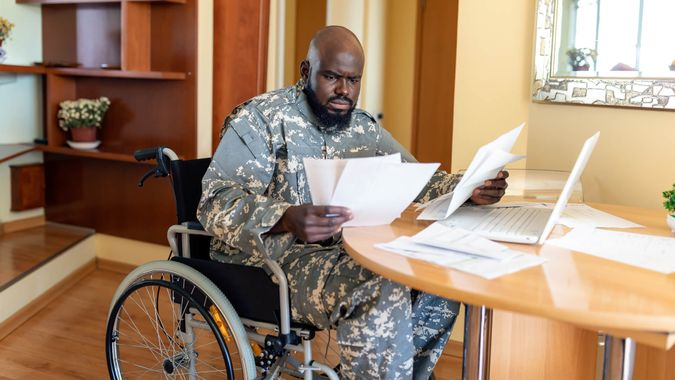 A Mature man of African American ethnicity with physical disabilities is sitting in wheelchair, worried in the home office.