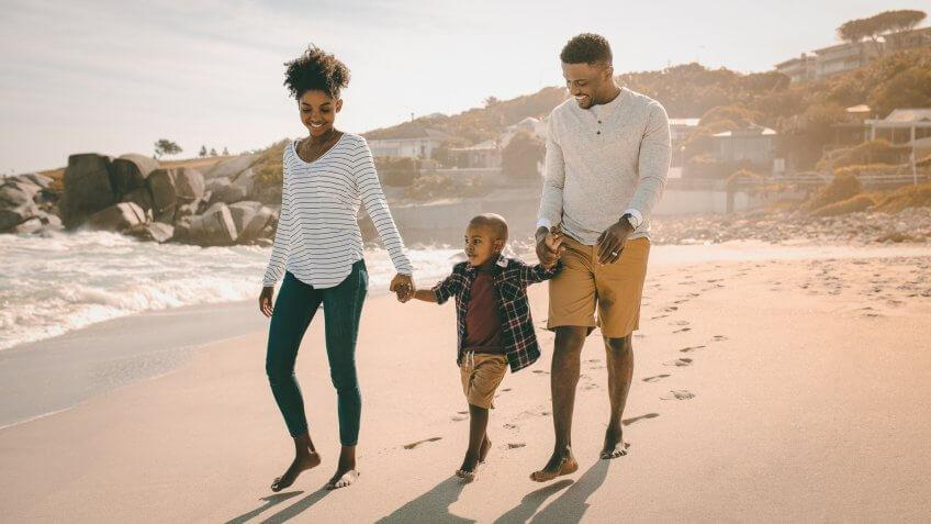 mom and dad walking on beach with son on vacation