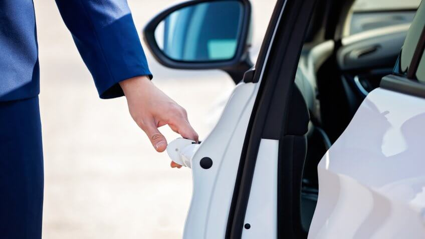 Young businessman opening white car door.