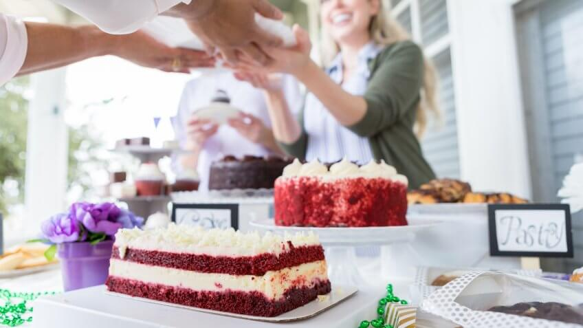 Cheerful female volunteer serves cake during a cancer awareness fundraising event.