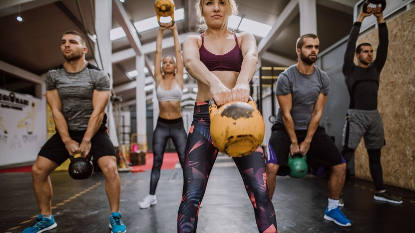 Sports People Squatting With Kettlebells On Gym Training.
