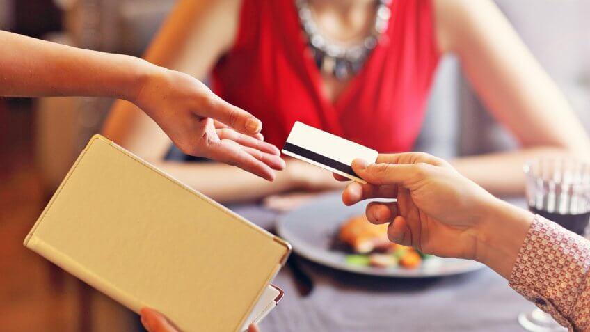 Picture showing people paying in restaurant by credit card reader.