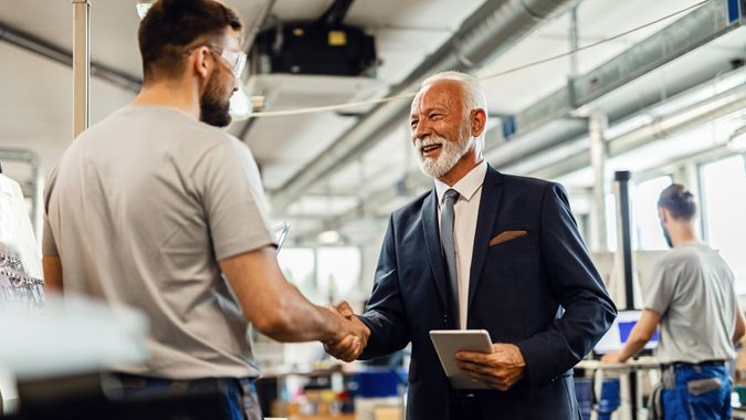 Happy senior businessman handshaking with manual worker in a factory.